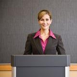 Donna di affari che si leva in piedi dietro il podio Immagine Stock