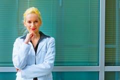 Donna di affari che si leva in piedi l'edificio per uffici vicino Immagine Stock