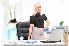 Donna di affari che si leva in piedi vicino allo scrittorio con il computer portatile Fotografia Stock