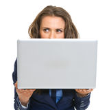 Donna di affari che si nasconde dietro il computer portatile Fotografia Stock Libera da Diritti