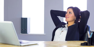 Donna di affari che si rilassa al suo scrittorio Fotografia Stock