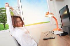Donna di affari che si rilassa con le mani dietro la o capa e di seduta lei fotografie stock