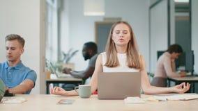 Donna di affari che si rilassa dopo il lavoro in ufficio Donna esaurita che fa il respiro di yoga archivi video