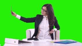 Donna di affari che si siede ad uno scrittorio nell'ufficio su un fondo verde Era fotografie sorridenti di se stessa su lei video d archivio
