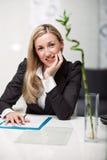 Donna di affari che si siede al suo scrittorio Immagine Stock
