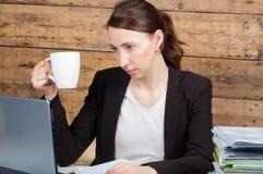 Donna di affari che si siede al suo scrittorio e che lavora alla tenuta del computer portatile Fotografie Stock