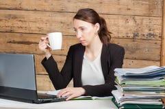 Donna di affari che si siede al suo scrittorio e che lavora alla tenuta del computer portatile Immagini Stock