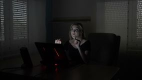 Donna di affari che si siede al suo scrittorio che simula un'interazione con un ologramma con lo schermo aumentato di realtà sul  video d archivio
