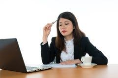 Donna di affari che si siede alla scrivania Immagini Stock