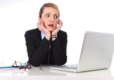 Donna di affari che si siede alla scrivania che funziona con il computer portatile nello sforzo che sembra turbato Fotografie Stock