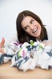 Donna di affari che si siede alla tavola con la carta dei rifiuti Immagini Stock