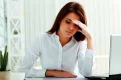Donna di affari che si siede alla tavola sul suo posto di lavoro Fotografie Stock Libere da Diritti