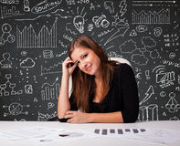 Donna di affari che si siede allo scrittorio con lo schema e le icone di affari Fotografia Stock