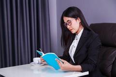Donna di affari che si siede allo scrittorio e che legge un libro Fotografia Stock Libera da Diritti