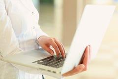 Donna di affari che si siede con il computer portatile immagini stock