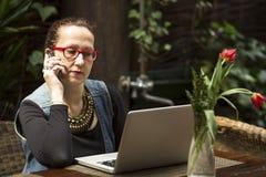 Donna di affari che si siede con il computer portatile alla tavola in un caffè comunicazione Immagine Stock Libera da Diritti