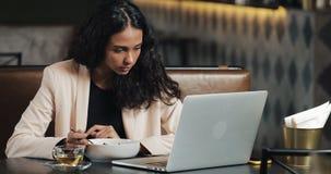 Donna di affari che si siede con un computer portatile nel caffè e che mangia cena con una tazza di tè sulla tavola Cibo del pran immagine stock