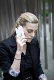 Donna di affari che si siede e che parla sul telefono Immagini Stock Libere da Diritti