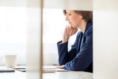 Donna di affari che si siede leggendo un documento Fotografia Stock