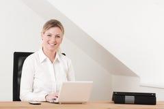 Donna di affari che si siede nel Ministero degli Interni con il computer portatile Immagini Stock