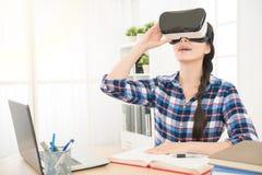 Donna di affari che si siede nell'ufficio e che tiene VR Fotografie Stock Libere da Diritti