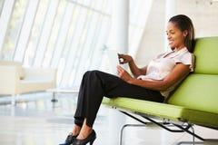 Donna di affari che si siede nell'ufficio moderno facendo uso della compressa di Digital Immagine Stock