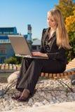 Donna di affari che si siede su un banco Fotografie Stock