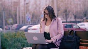 Donna di affari che si siede sul banco e che utilizza computer portatile nel fondo del parco della città stock footage