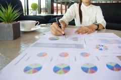 Donna di affari che si siede sul lavoro che indica il grafico fotografia stock