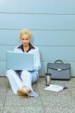 Donna di affari che si siede sul pavimento all'edificio per uffici immagine stock