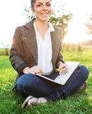Donna di affari che si siede sull'erba Immagini Stock Libere da Diritti