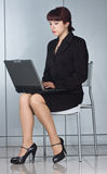 Donna di affari che si siede sulla presidenza con il computer portatile immagine stock libera da diritti