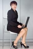 Donna di affari che si siede sulla presidenza con il computer portatile immagini stock