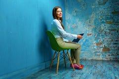 Donna di affari che si siede sulla sedia con il computer portatile nella stanza d'annata Fotografie Stock