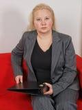 Donna di affari che si siede in un sofà Fotografia Stock