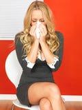 Donna di affari che si siede in una sedia che soffia il suo naso Fotografia Stock Libera da Diritti