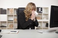 Donna di affari che soffia il suo naso al suo scrittorio Fotografia Stock