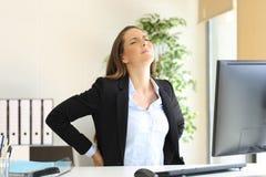 Donna di affari che soffre dolore posteriore immagine stock