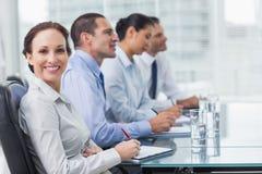 Donna di affari che sorride alla macchina fotografica mentre i suoi colleghi t d'ascolto Immagini Stock Libere da Diritti