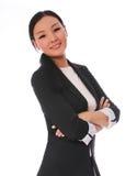Donna di affari che sorride con le armi attraversate isolate su fondo bianco. bella donna asiatica in vestito nero Fotografia Stock