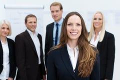 Donna di affari che sorride con un gruppo dietro lei Immagine Stock Libera da Diritti