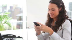 Donna di affari che sorride mentre redigendo un messaggio di testo Immagini Stock