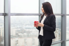 Donna di affari che sta alla finestra con la tazza Fotografia Stock