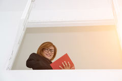 Donna di affari che sta contro il libro di lettura della finestra nella sua stanza Fotografia Stock Libera da Diritti