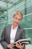 Donna di affari che sta davanti alla costruzione di casa immagini stock