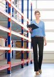 Donna di affari che sta dentro accanto agli scaffali in magazzino con la lavagna per appunti Fotografia Stock