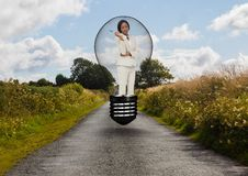 Donna di affari che sta nella lampadina sopra la strada contro il cielo Immagine Stock Libera da Diritti