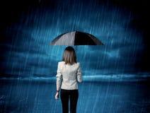 Donna di affari che sta in pioggia con un ombrello fotografie stock libere da diritti