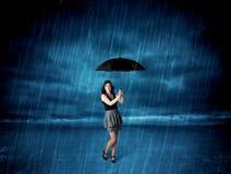 Donna di affari che sta in pioggia con un ombrello immagine stock libera da diritti