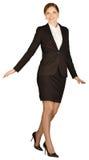 Donna di affari che sta su su un gamba e sguardo Immagine Stock